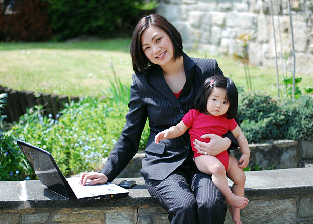 A businesswoman juggles career and motherhood as she holds her 10 month old girl while checking her email.